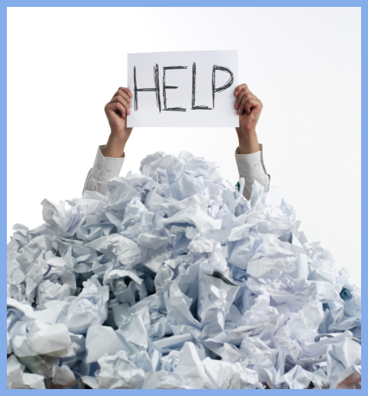 Picture of a man's arms emerging from a large pile of discarded papers, holding a Help sign.